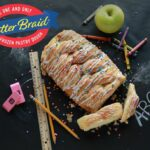24/7 MOMS giveaway - butter braid pastry with icing on chalkboard with school supplies and butter braid logo
