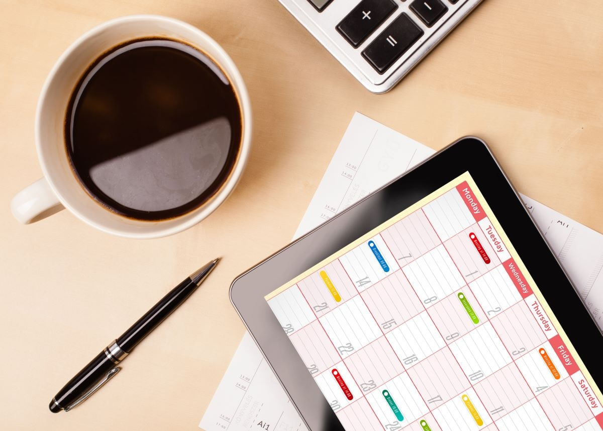 How Long Should Your Fundraiser Be? Desk close-up with cup of coffee, pen, calculator, and tablet with a calendar on it.